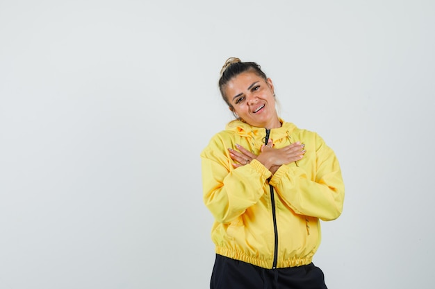 Kobieta trzymająca się za ręce na piersi w sportowym garniturze i wyglądająca na wdzięczną. przedni widok.