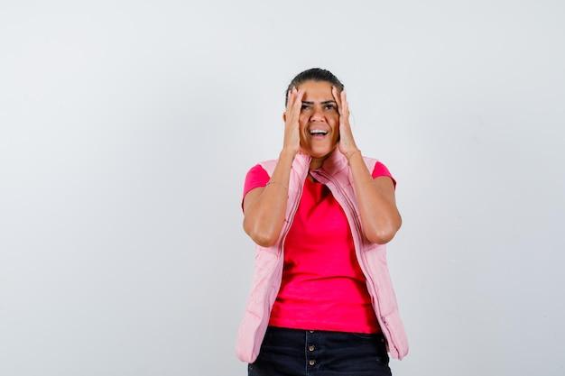 Kobieta trzymająca się za ręce nad twarzą w koszulce, kamizelce i wyglądająca na szczęśliwą