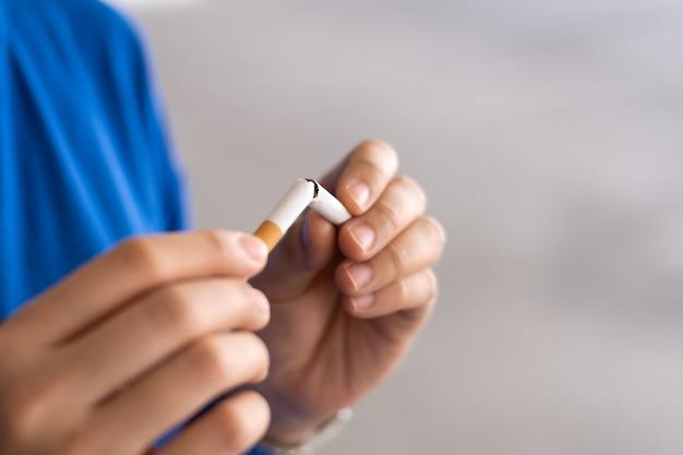 Kobieta trzymająca się za ręce trzymająca i łamiąca papierosa w celu rzucenia palenia rzuć palenie dla zdrowia