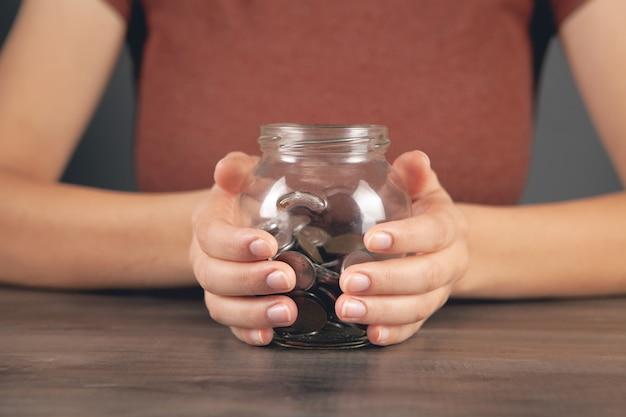 Kobieta trzymająca słoik z oszczędnościami przy stole