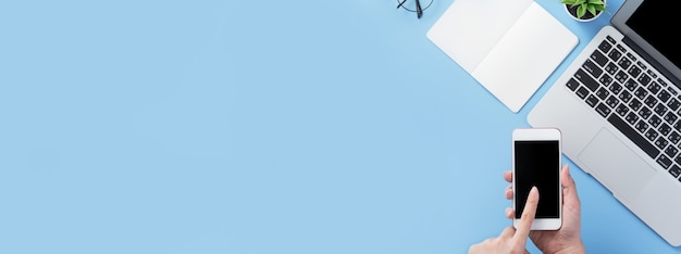 Kobieta trzymająca smartfon z minimalnym niebieskim biurkiem, koncepcja zakupów online, płatności internetowe, handel elektroniczny
