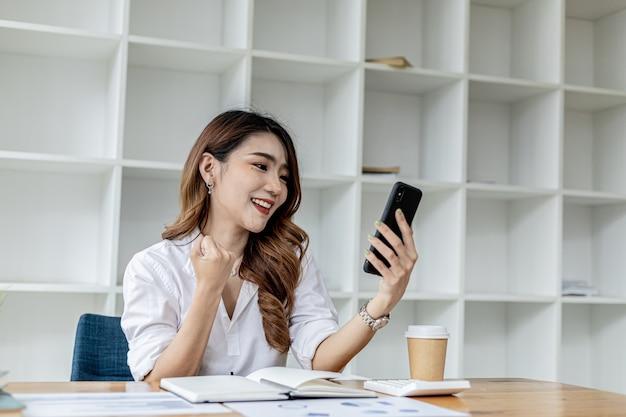 Kobieta trzymająca smartfona i gestykulująca, azjatycka kobieta biznesu okazująca radość po obserwowaniu rosnących zarobków firmy w ciągu ostatniego miesiąca, zarządza rozwojem. koncepcja administracji biznesowej.