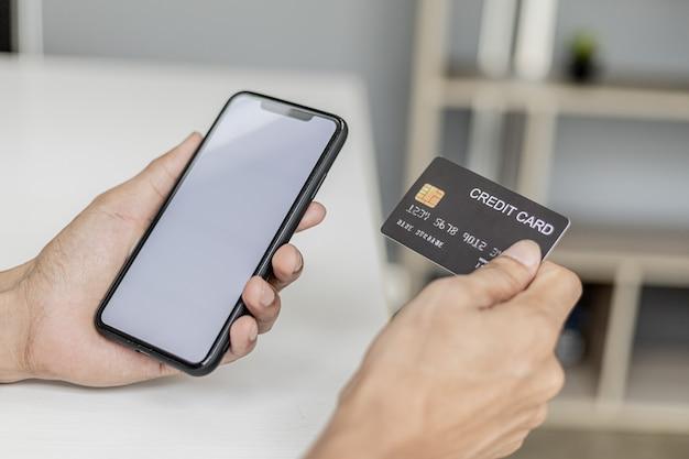 Kobieta trzymająca smartfona i kartę kredytową, wpisuje informacje o swojej karcie kredytowej, aby zapłacić za zakupy dokonane za pomocą aplikacji na smartfona. zakupy online i koncepcja płatności kartą kredytową.