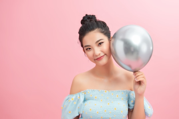 Kobieta trzymająca srebrny balon na różowym tle