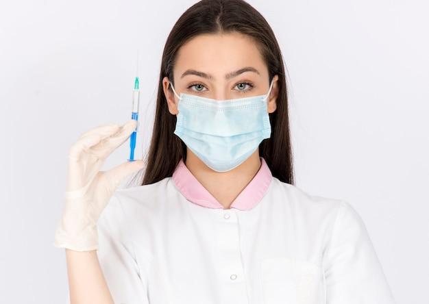 Kobieta trzymająca strzykawkę ze szczepionką, nosząca maskę i rękawiczki, szczepionka przeciwko wirusowi koronawemu, czas pandemii