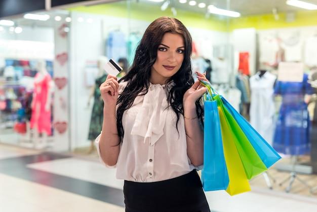 Kobieta trzymająca torby na zakupy przez ramię i kartę kredytową