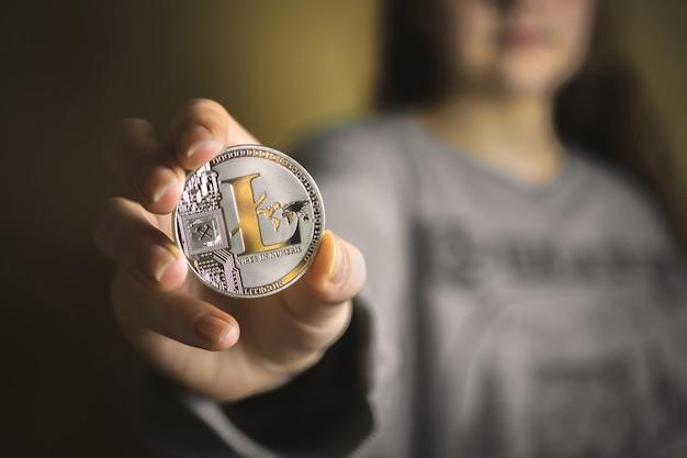 Kobieta trzymająca w dłoni fizyczną kryptowalutę litecoin, widok zbliżenia