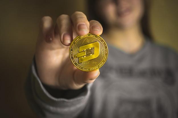 Kobieta trzymająca w dłoni fizyczną kryptowalutę monety, widok zbliżenia