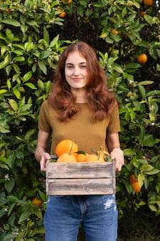 Kobieta trzymająca w dłoniach pudełko pełne pomarańczy