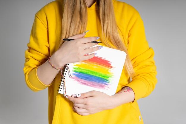 Kobieta trzymająca w dwóch rękach notatnik z tęczą lgbtq
