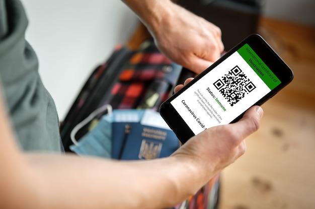 Kobieta trzymająca w jednej ręce telefon komórkowy makietę cyfrowego świadectwa szczepień w jednej ręce i paszportu, maski i biletu w drugiej