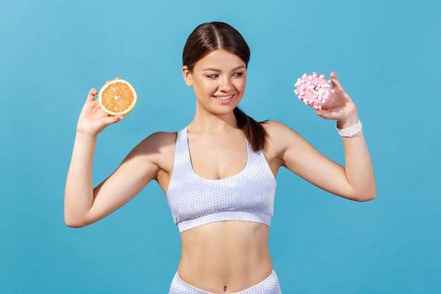 Kobieta trzymająca w rękach połowę grejpfruta i pączka, patrząca na śmieciowe słodkie ciasto z pokusą