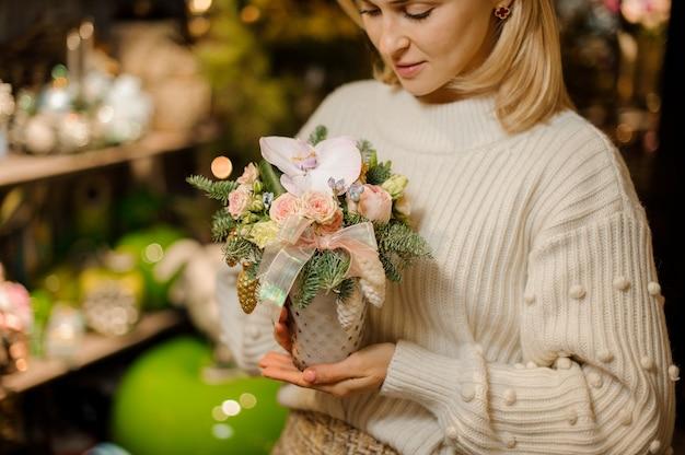 Kobieta trzymająca wazon z gałęziami jodły, kremowymi różami, orchideą i zabawkami w kształcie stożka