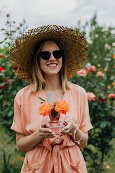 Kobieta trzymająca wazon z pomarańczowymi różami
