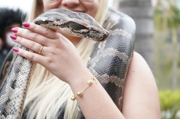 Kobieta trzymająca wielkiego węża na ramionach i dłoniach