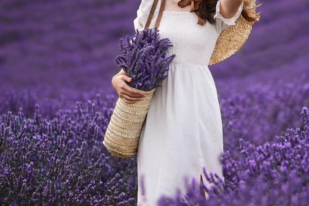 Kobieta trzymająca wiklinowy kosz z lawendą w polu