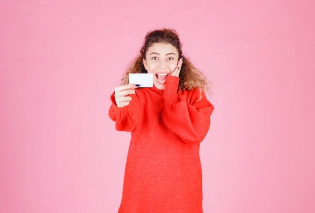 Kobieta trzymająca wizytówkę wygląda na bardzo szczęśliwą i zdziwioną.