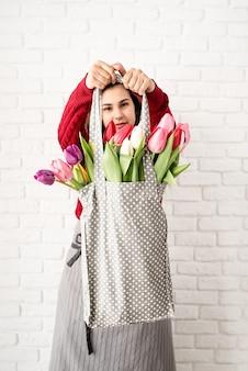 Kobieta trzymająca worek z szarego materiału w kropki w kolorowe tulipany