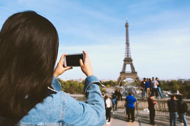 Kobieta turysta bierze fotografię telefonem blisko wieży eifla w paryż pod światłem słonecznym i niebieskim niebem. znane popularne miejsce turystyczne na świecie.