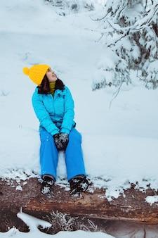 Kobieta turysta ciesząca się widokiem na ośnieżoną zimową przestrzeń leśną