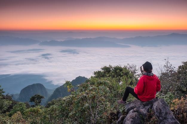 Kobieta turysta siedzi zwiedzanie na wzgórzu z mgłą o wschodzie słońca w sanktuarium dzikiej przyrody