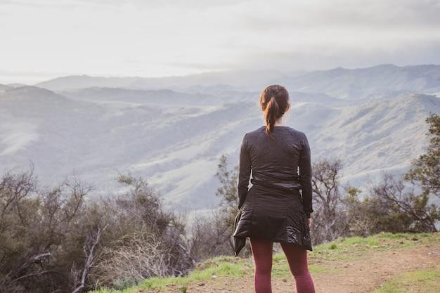 Kobieta turysta stojąca na szczycie szlaku turystycznego gaviota peak zrobionego w kalifornii, usa