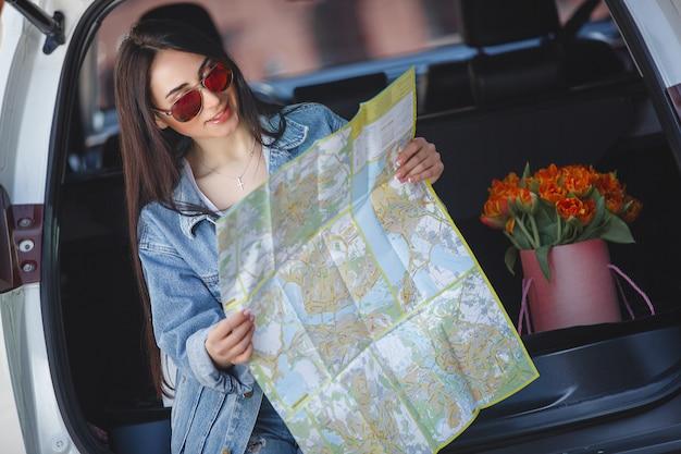 Kobieta turysta trzyma mapę miasta. podróżujący samochodem w nieznanym kraju. dziewczyna jedzie samochodem.