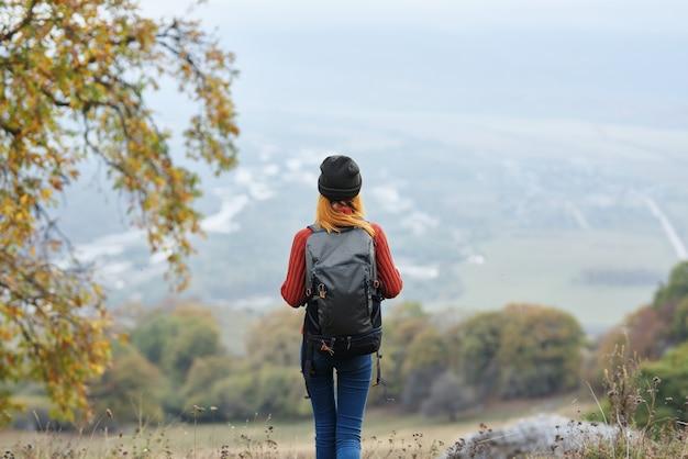 Kobieta turysta w górach jesień drzewa wakacje