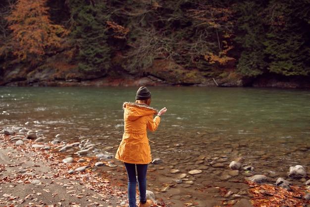 Kobieta turysta w pobliżu gór rzeki jesienią