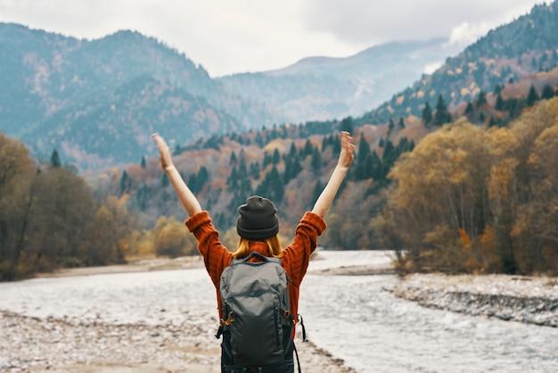 Kobieta turysta w pobliżu rzeki z rękami podniesionymi góry krajobraz. zdjęcie wysokiej jakości