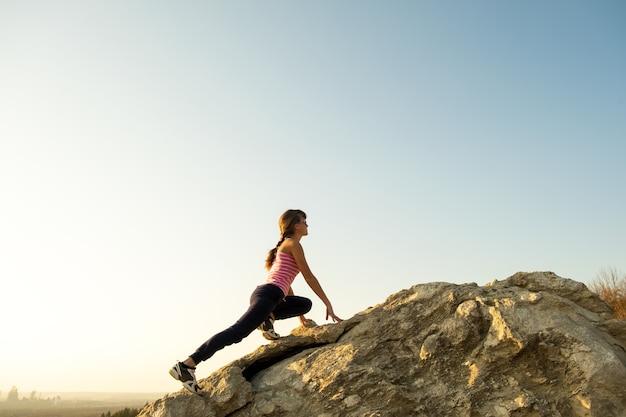 Kobieta turysta wspinaczka stroma duża skała w słoneczny dzień. młoda wspinaczka pokonuje trudną drogę wspinaczkową. aktywny wypoczynek w koncepcji przyrody.