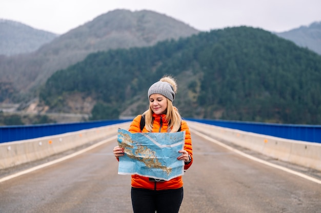 Kobieta Turysta Z Mapą Spaceru Na Drodze Z Zielonym Górskim Krajobrazem Premium Zdjęcia