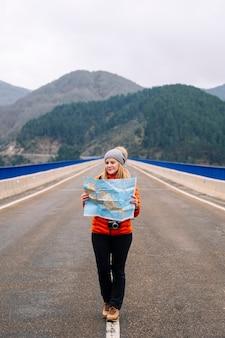 Kobieta turysta z mapą spaceru na drodze z zielonym górskim krajobrazem