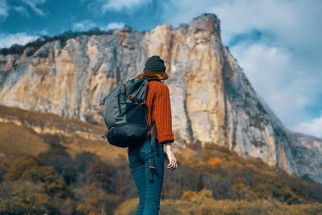 Kobieta turysta z plecakiem na jesień sezon podróży natura