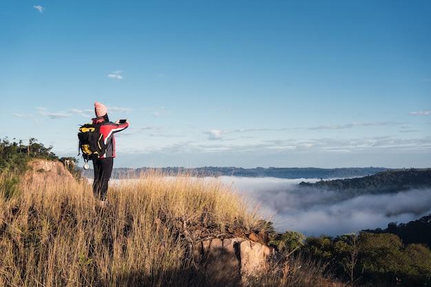 Kobieta turysta z plecakiem na szczycie góry i robiąca zdjęcie doliny.