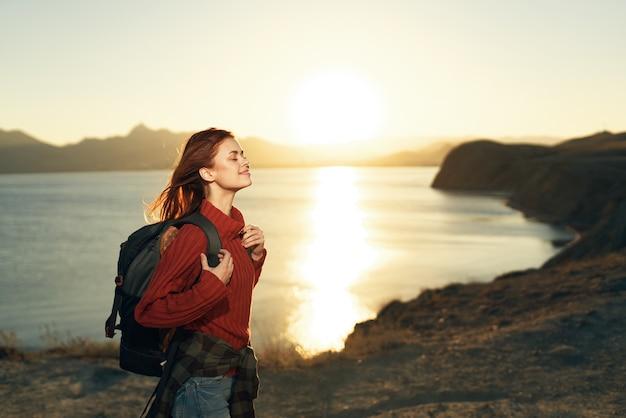Kobieta turysta z plecakiem na zewnątrz krajobraz zachód słońca podróż