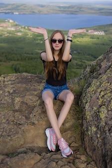 Kobieta turysta z plecakiem siedzi na szczycie góry, ciesząc się widokiem w ciągu dnia.