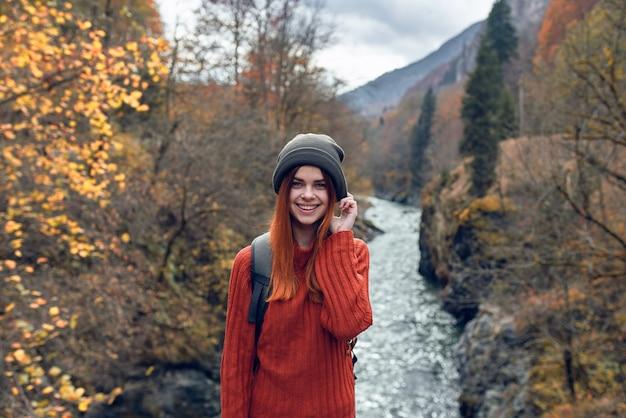 Kobieta turysta z plecakiem w pobliżu rzeki góry jesienny las podróż forest