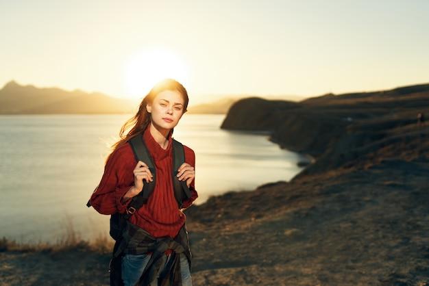 Kobieta turysta zachód słońca horyzont góry skaliste świeże powietrze
