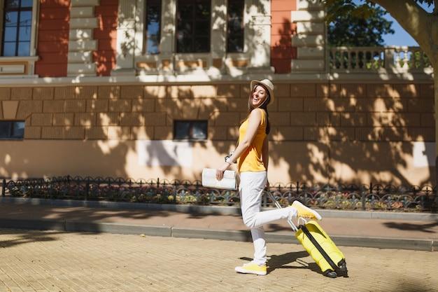Kobieta turystyczna ładna podróżnik w żółtym letnim kapeluszu dorywczo ubrania z mapą miasta walizka spaceru w mieście na świeżym powietrzu. dziewczyna wyjeżdża za granicę na weekendowy wypad. koncepcja życia podróż turystyka.