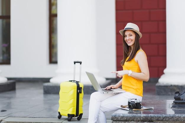 Kobieta turystyczna młody podróżnik w ubranie, kapelusz z walizką siedzieć, wskazując palcem wskazującym na komputerze typu laptop w mieście na świeżym powietrzu. dziewczyna wyjeżdża za granicę na weekendowy wypad. styl życia podróży turystycznej.