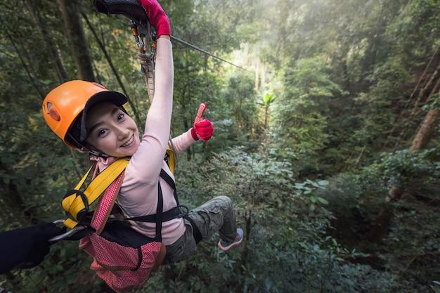 Kobieta turystycznych noszenia odzieży casual na zamek błyskawiczny lub baldachim doświadczenie w laos rainforest, azja