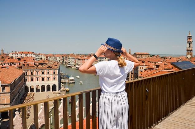Kobieta turystycznych podróży we włoszech. zobacz na canal grande. młoda dziewczyna z słomkowym kapeluszem w wenecji. dziewczyna podróżuje do wenecji, patrząc na dachu