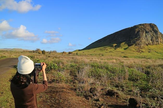 Kobieta turystycznych robienia zdjęć wulkanu rano raraku