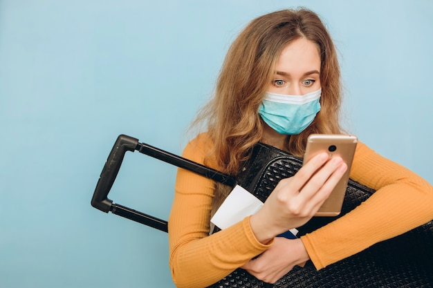Kobieta turystycznych w masce medycznej siedzi z bagażem w ręku. wybuch covid-19 koronawirusa. koncepcja podróży i korony. turysta nie może wyjechać z powodu pandemii.