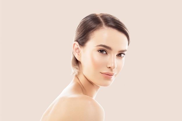 Kobieta twarz piękna ręka dotyka zdrowej skóry naturalny makijaż piękne kobiece beżowe tło
