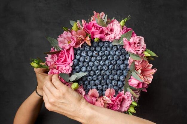 Kobieta tworzy bukiet jagód i różowych kwiatów w kółko