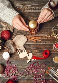 Kobieta tworzy stylowe prezenty świąteczne, udekoruj świeczkę cynamonem
