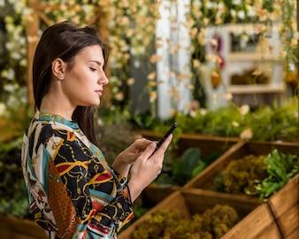 Kobieta używa smartphone w zielonym domu