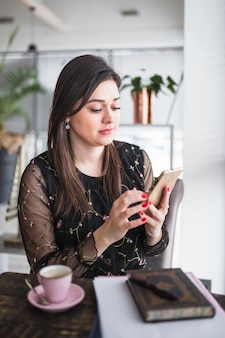 Kobieta używa telefon komórkowego w sklep z kawą